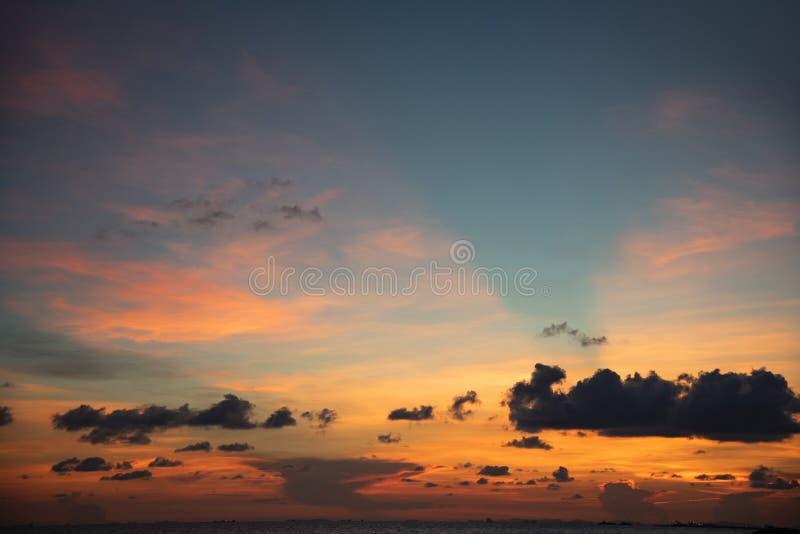 Färgrik apelsin för härligt moln för himmelsolnedgångkontur och blå dramatisk himmelbakgrund på tropisk havssommar royaltyfria foton