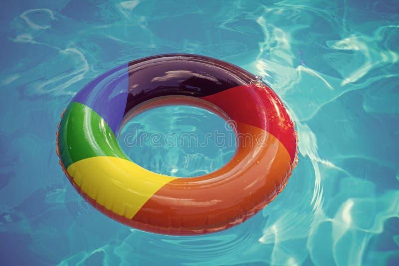 färgrik badcirkel eller livboj Uppblåsbar cirkelflöte i blått vatten för pöl Sommarsemester och lopp till havet, Bahamas royaltyfri fotografi