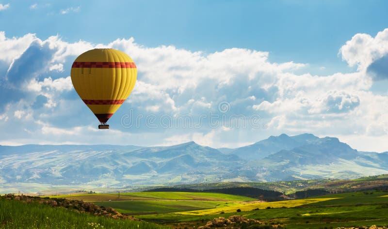 Färgrik ballong för varm luft som flyger över grönt fält fotografering för bildbyråer
