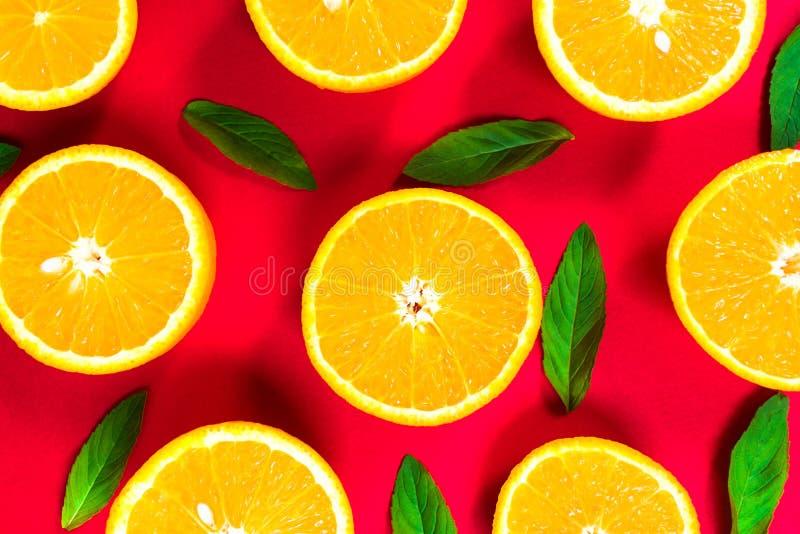 Färgrik bild av orange skivor och mintkaramellsidor på en röd bakgrund Top besk?dar royaltyfri foto