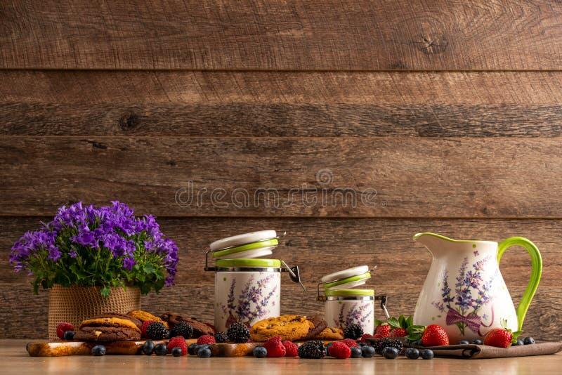 Färgrik blandad blandning av lösa bär, violetta blommor, chokladkakor och keramiska skyttlar royaltyfri foto