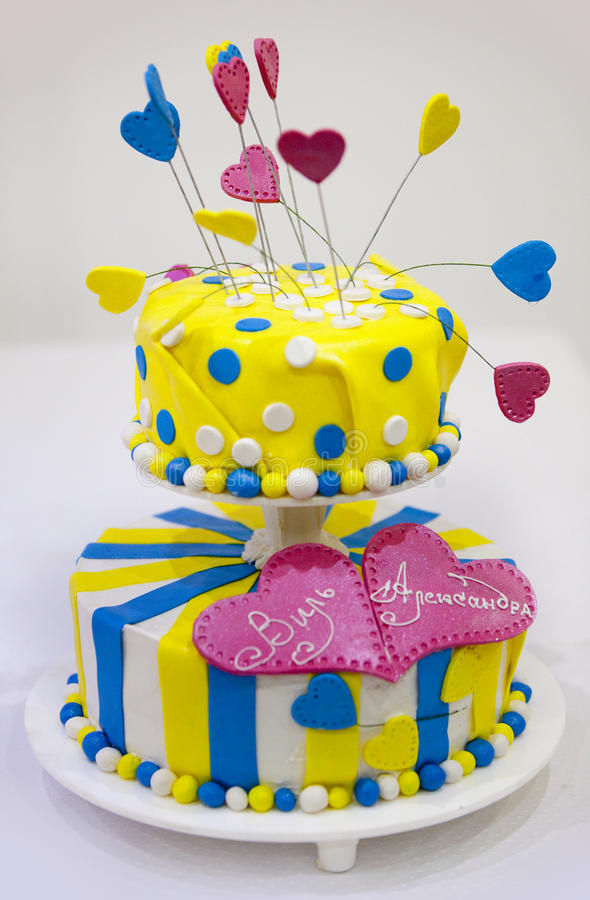 Färgrik bröllopstårta - gulna, slösa, rosa färger - med vita prickar och hjärtor royaltyfria foton