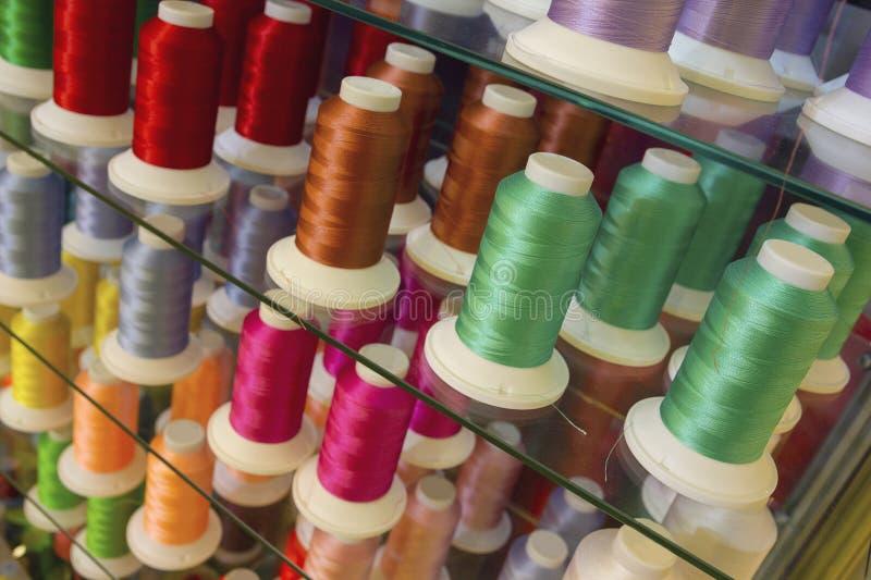 Färgrik broderitrådrulle genom att använda i plaggbransch, rad av mångfärgade garnrullar som syr material royaltyfria foton