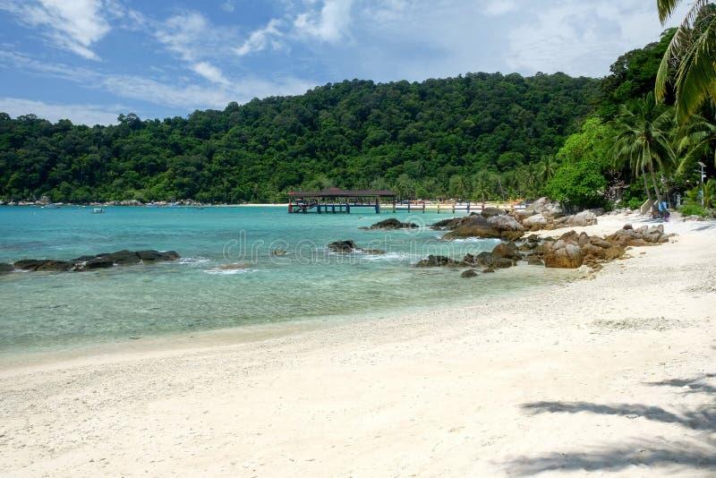 Färgrik brygga i en fjärd på en vit sandig tropisk strand och blått royaltyfri foto