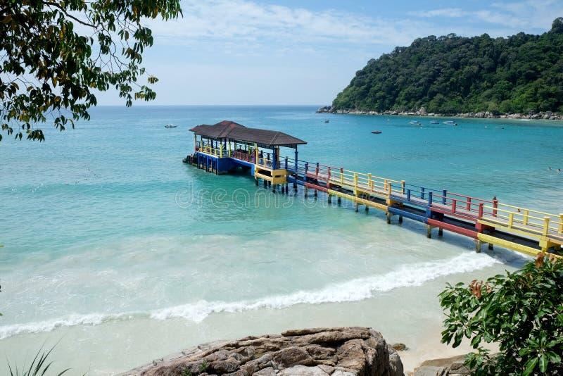 Färgrik brygga på ett vitt sandigt tropiskt strand- och blåtthav royaltyfri bild