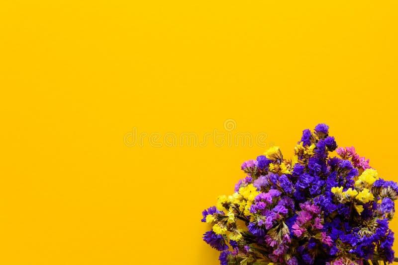 Färgrik bukett av torkade höstblommor som ligger på gulingpappersbakgrund kopiera avstånd Lekmanna- lägenhet Top beskådar arkivbild