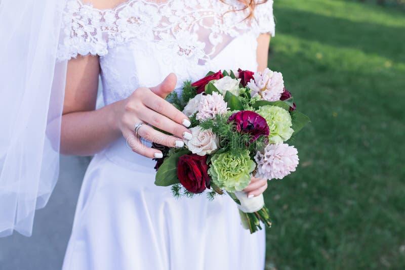 Färgrik bukett för härligt bröllop i händer av bruden Moderiktiga och moderna bröllopblommor En vigselring på fingret av bet fotografering för bildbyråer