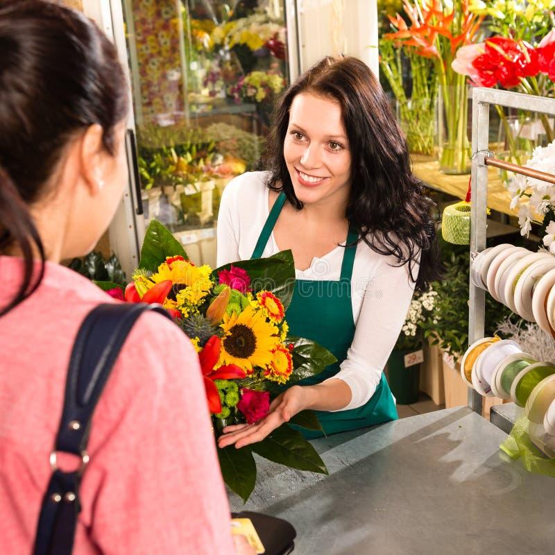 Färgrik bukettblomsterhandlarekvinna som säljer kundblomman royaltyfria bilder