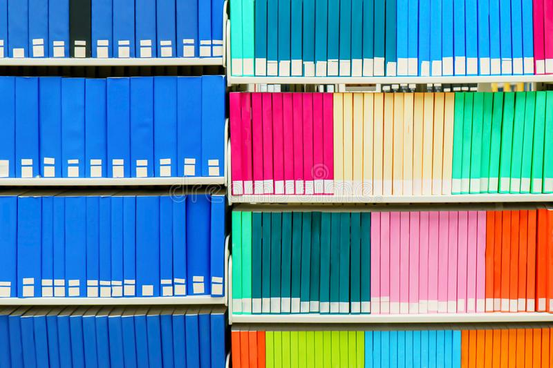 Färgrik bunt av forskningböcker i ett universitetarkiv, med tomma bokryggar Anv?ndbart som en bakgrund arkivfoto