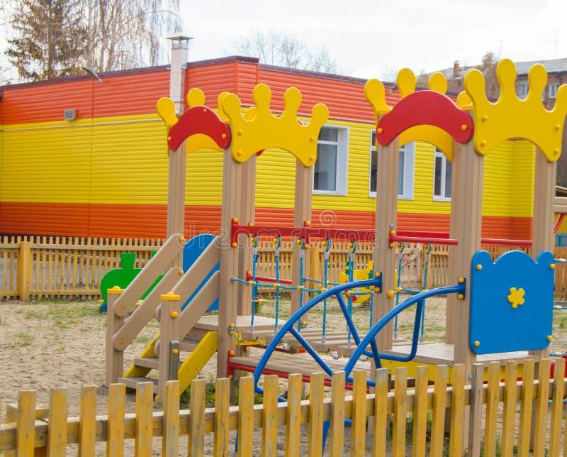 Färgrik children& x27; s-lekplats i solen, en lekstuga och en glidbana fotografering för bildbyråer