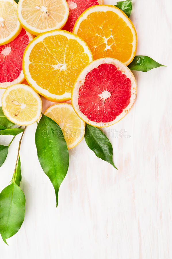 Färgrik citrusfruktskiva med gräsplansidor på vit träbakgrund, hörn arkivfoto
