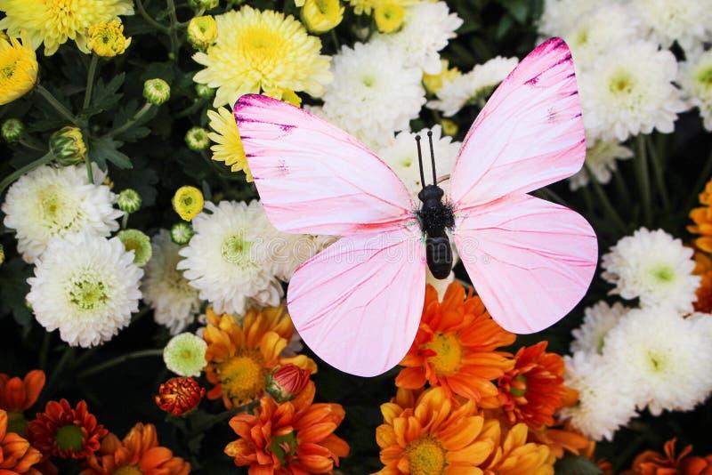 Färgrik dekorativ rosa konstgjord fjäril i trädgårdblommor royaltyfri foto