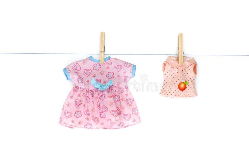 Färgrik dockakläder som hänger på klädstrecket Isolerad bild royaltyfri bild