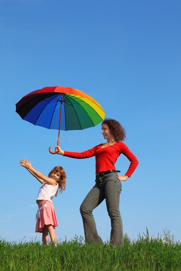 färgrik dotter henne holdingmoder över paraplyet royaltyfria bilder