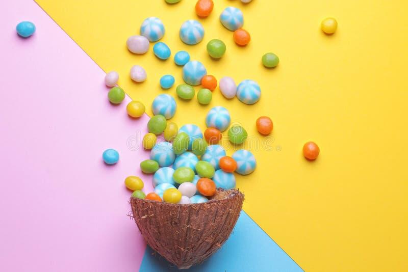 Färgrik explosion av sötsaker i en kokosnöt på ljusa mång--färgade bakgrunder, idérik stilleben arkivbild