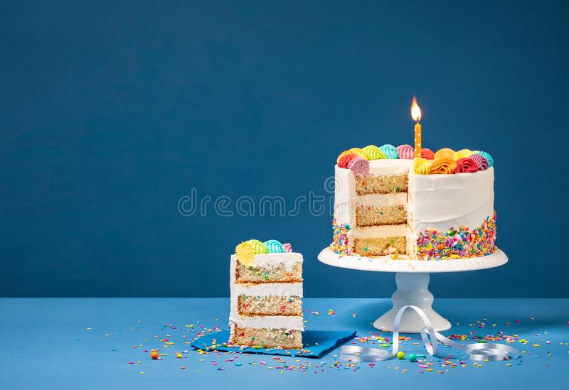 Färgrik födelsedagkaka med skivan och stänk royaltyfri foto