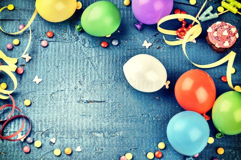 Färgrik födelsedagram med flerfärgade partiobjekt på mörker - blått royaltyfria bilder