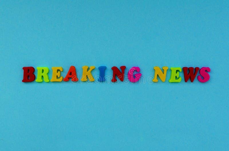 Färgrik ` för text`-breaking news av magnetiska bokstäver på bakgrund för blått papper royaltyfri foto