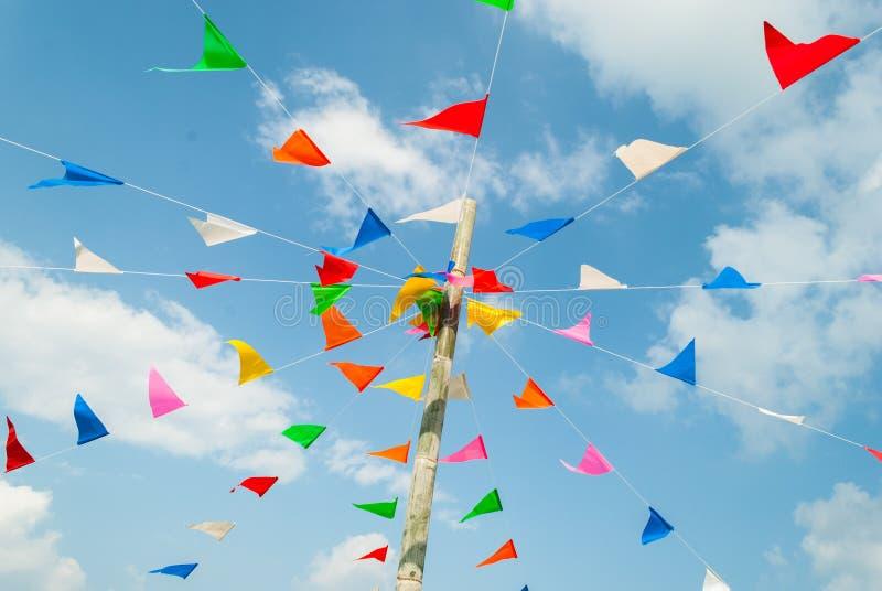 Färgrik festlig bunting sjunker mot, på blått och fördunklar himmel royaltyfri fotografi