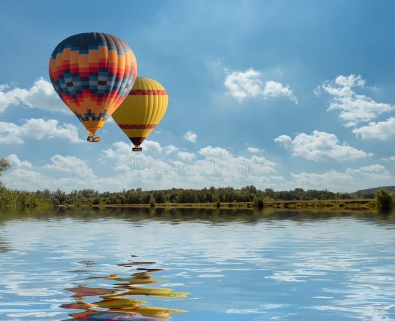 Färgrik fluga för ballong för varm luft över den blåa sjön med reflexion royaltyfri bild