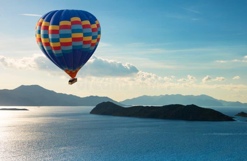 Färgrik fluga för ballong för varm luft över det blåa havet royaltyfria foton
