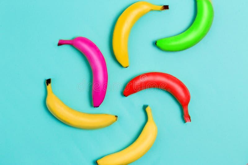 Färgrik fruktmodell av ny guling, röda, rosa gröna bananer på blå bakgrund Från bästa sikt royaltyfria foton