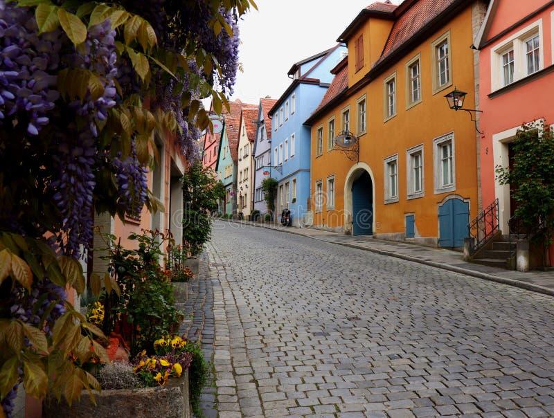 Färgrik gata med vårblommor i Rothenburg obder Tauber, Tyskland royaltyfri foto