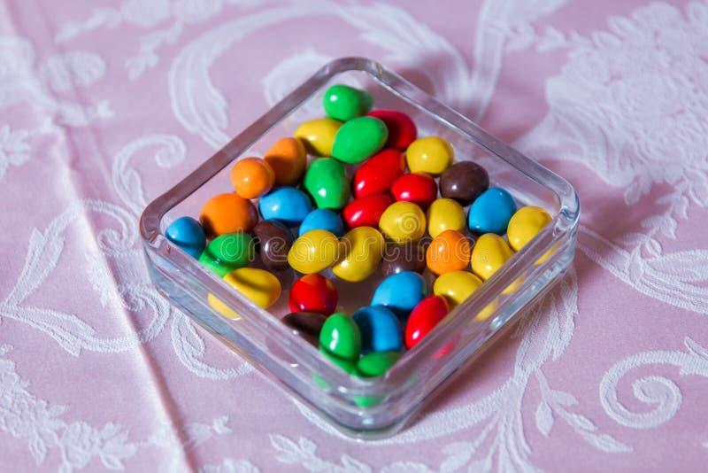 färgrik godis Mång- kulöra sötsaker Kulör godis i ett exponeringsglas Rund choklad är mycket färgrik royaltyfria bilder