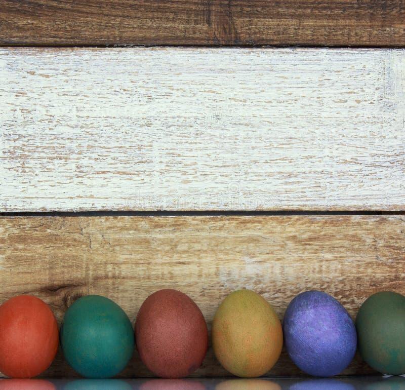 Färgrik gräns för påskägg som visas på ett mång- kulört träB royaltyfria bilder