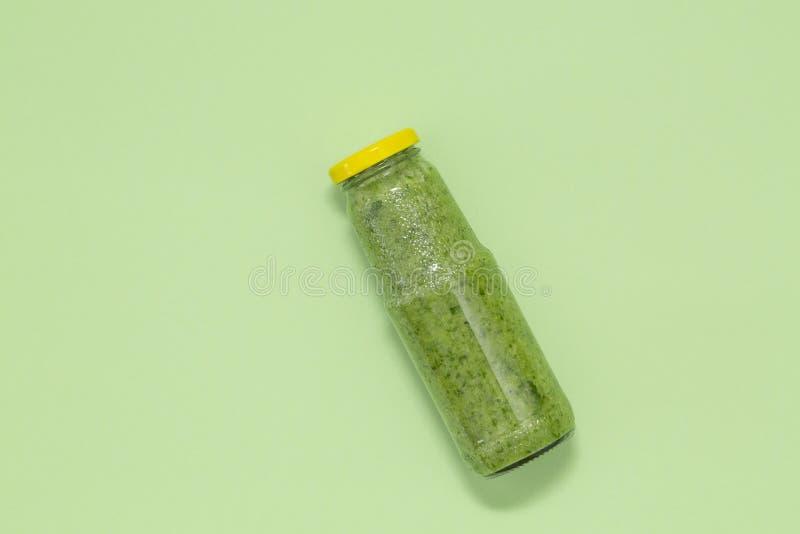 Färgrik grön smoothie i flaska på grön bakgrund, bästa sikt royaltyfri foto