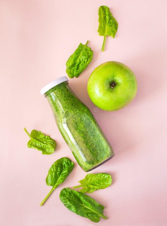 Färgrik grön smoothie i flaska på rosa bakgrund, bästa sikt royaltyfri foto