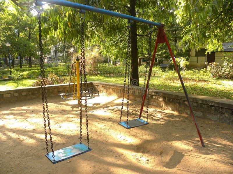 Färgrik gungauppsättning på lekplatsen för barn fotografering för bildbyråer