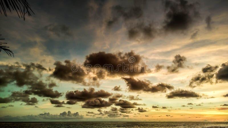 Färgrik himmel med solnedgången Härlig solnedgång i den Menganti stranden, Kebumen, centrala Java, Indonesien royaltyfri bild