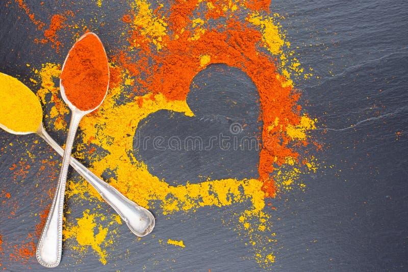 Färgrik hjärta från kryddor på svart bakgrund med två tappningskedar Föreslå valentindagbegrepp royaltyfria bilder