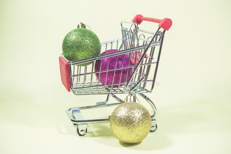 Färgrik jul klumpa ihop sig i den lilla metallshoppingvagnen på arkivbild
