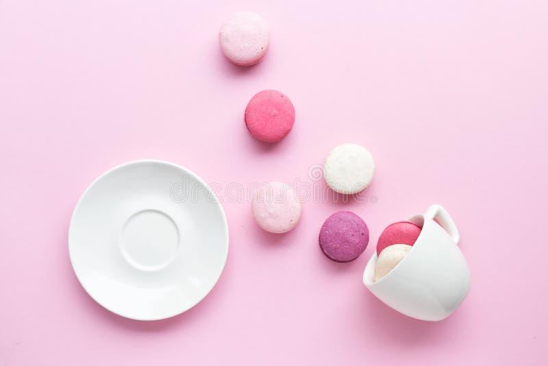 Färgrik kakamacaron eller makron som isoleras över bakgrund för pastellfärgade rosa färger Top beskådar royaltyfri fotografi