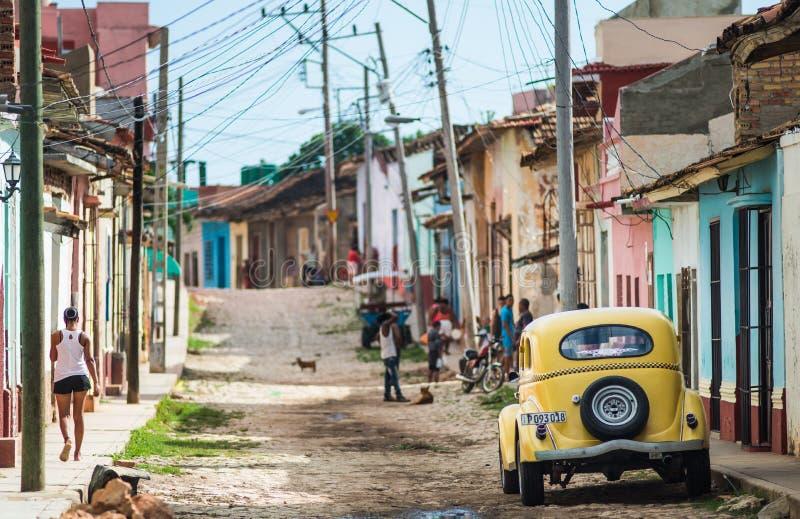 Färgrik karibisk åldrig by med kullerstengatan, den klassiska gula bilen och det koloniala huset, Trinidad, Kuba, Amerika royaltyfri foto