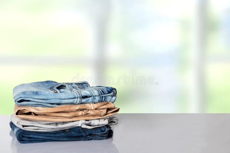 Färgrik kläder för bunt Hög av färgrik jeans på vita tabellwi arkivbild