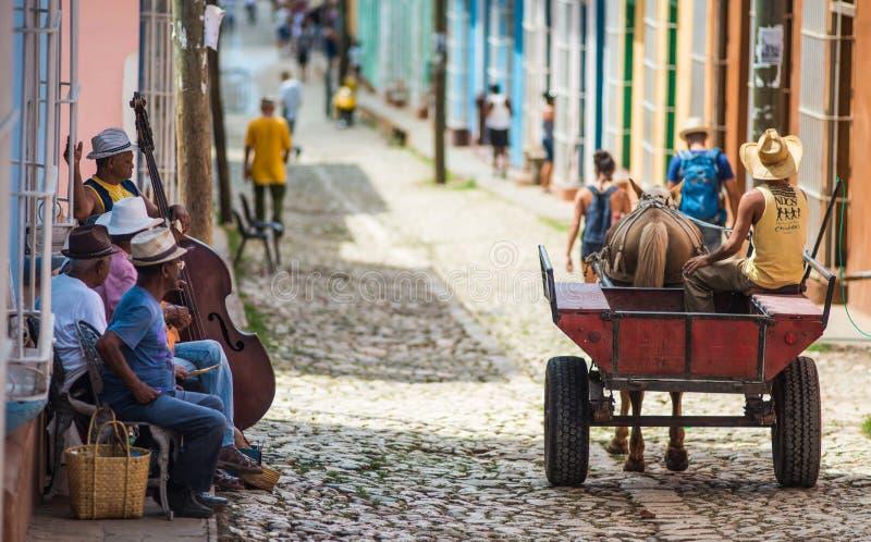 Färgrik kolonial forntida stad med den klassiska vagnen, bonde, kullerstengata i Trinidad, Kuba, Amerika royaltyfri fotografi