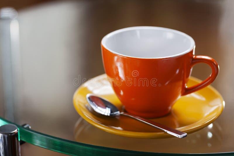 Färgrik kopp av cappuccino på en exponeringsglastabell royaltyfri fotografi