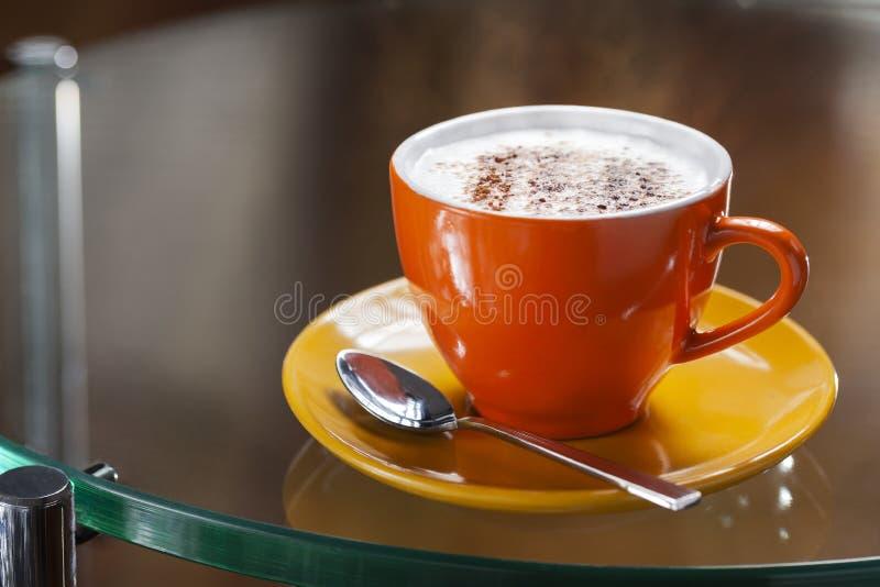 Färgrik kopp av cappuccino på en exponeringsglastabell fotografering för bildbyråer