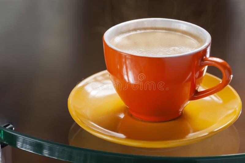 Färgrik kopp av cappuccino på en exponeringsglastabell arkivbilder
