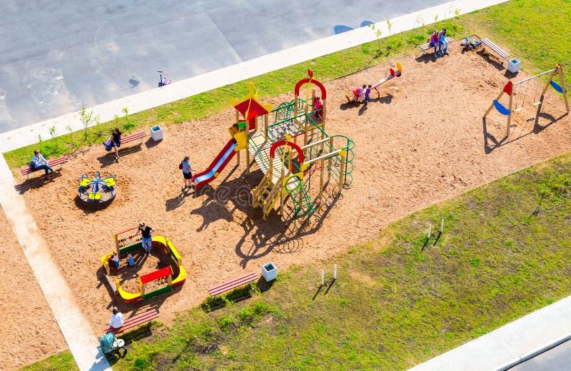 Färgrik lekplats för barn` s för ungar i nytt bostadsområde royaltyfri foto