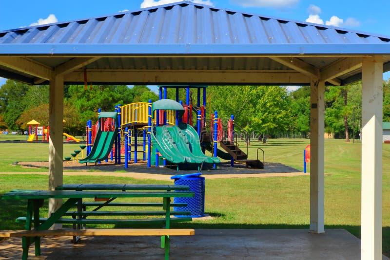 Färgrik lekplatsutrustning i ett offentligt parkerar med djupblå himlar royaltyfri bild