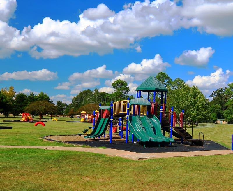 Färgrik lekplatsutrustning i ett offentligt parkerar med djupblå himlar arkivbilder