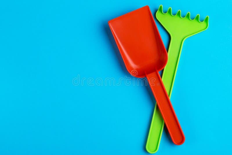 Färgrik leksakspade och att kratta på ljus blå bakgrund arkivbild