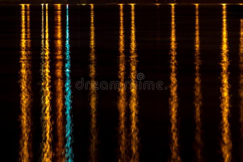 Färgrik ljus reflexion in i mörkt nattvatten royaltyfria bilder