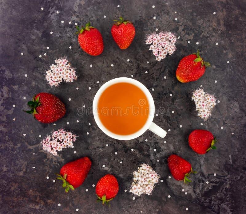 Färgrik ljus sammansättning av kopp te, nya jordgubbar och lösa blommor Lekmanna- lägenhet arkivbild
