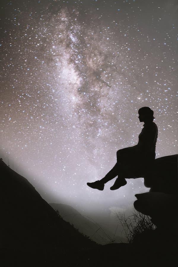 Färgrik natthimmel med stjärnor och konturn av en stående flicka som sitter på stenen Blå mjölkaktig väg med flickan på berget royaltyfri foto
