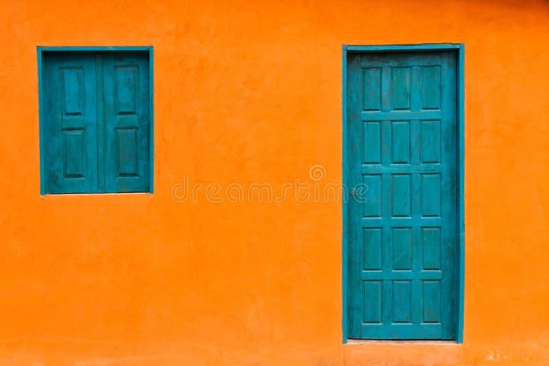 Färgrik och enkel orange fasad med den blåa grönaktiga dörren och Windows arkivbilder